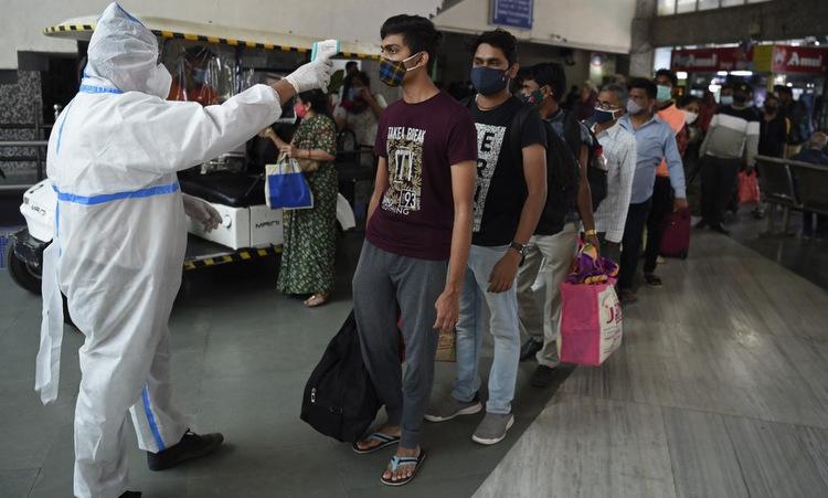 Kiểm tra thân nhiệt tại ga tàu ở Mumbai, Ấn Độ, hôm 19/12. Ảnh: AFP.